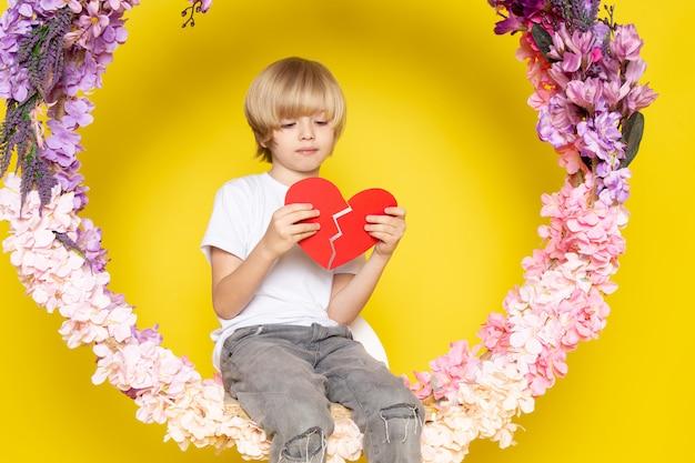 Een vooraanzicht blonde leuke jongen in de witte zitting van de de holdingshartvorm van het t-shirt op de bloem maakte tribune op de gele vloer