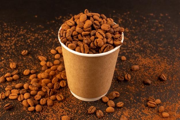 Een vooraanzicht bruine koffiezaden in plastic beker op het bruine oppervlak en de korrel van de koffiezaad donkere korrel