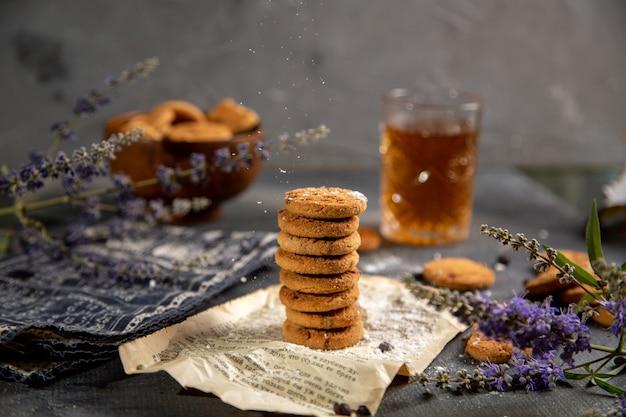 Een vooraanzicht bureau met koekjes en met thee op de grijze tafel koekjes thee koekje zoete suiker