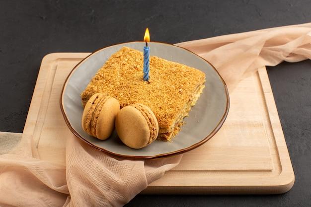 Een vooraanzicht cakeplak lekker en gebakken binnenplaat met kaars. macarons op het houten bureau en het donkere suikerzoete van het cakekoekje