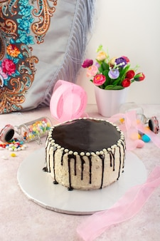 Een vooraanzicht chocoladetaart met snoepjes op het roze bureau