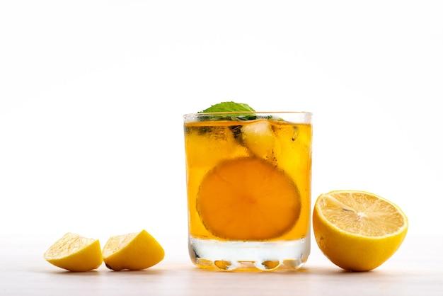 Een vooraanzicht citroendrank met verse citroenstukjes op wit, fruit citrus kleur