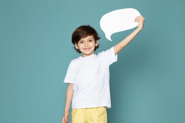 Een vooraanzicht dat leuke jongen glimlacht die wit teken in witte t-shirt op de blauwe ruimte houdt