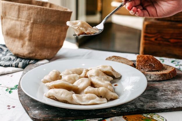 Een vooraanzicht deegmaaltijd met gehakt in gepekelde oosterse schotel met peper en brood loafs keukenvlees op het bruine houten bureau