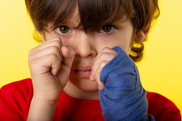 Een vooraanzicht dicht omhoog leuk kind in het rode t-shirt stellen in het in dozen doen op de gele muur