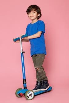 Een vooraanzicht die leuke jongen in blauwe t-shirt berijdende autoped op de roze vloer glimlachen