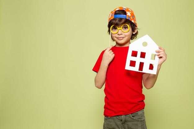 Een vooraanzicht die leuke jongen in rood het huisdocument van de t-shirtholding op de steen gekleurde ruimte glimlachen