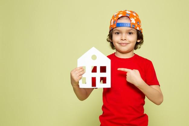 Een vooraanzicht die leuke jongen in rood t-shirt glimlachen en honkbal glb die huis gevormd document op de steen gekleurde ruimte houden