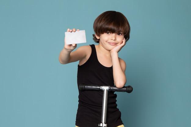 Een vooraanzicht die leuke jongen in zwarte t-shirt berijdende autoped glimlachen die witte kaart op de blauwe ruimte houden