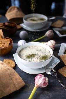 Een vooraanzicht dovga schotel met gedroogde munt in witte plaat samen met brood loafs eieren bloemen op tafel soep vloeistof heet op het grijze bureau