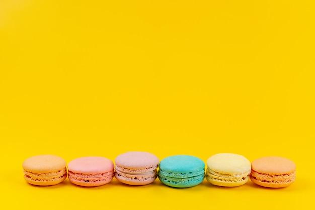Een vooraanzicht franse macarons kleurrijk heerlijk en gebakken op geel, cakekoekje banketbakkerij