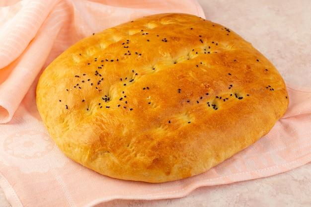 Een vooraanzicht gebakken brood heet smakelijk verpakt in roze handdoek op roze achtergrond bakkerij deeg ontbijt