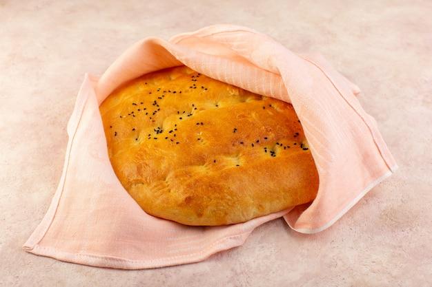 Een vooraanzicht gebakken brood heet smakelijk verpakt in roze handdoek op roze