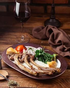 Een vooraanzicht gebakken vleesbeenderen met greens en tomaat op het bruine houten het voedselvlees van de bureaumaaltijd