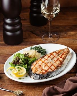 Een vooraanzicht gebakken vleesplak met citroen en greens op het bruine het voedselvlees van de bureaumaaltijd