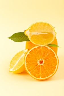 Een vooraanzicht geheel oranje en gesneden stuk samen met gesneden citroen rijpe verse sappige mellow geïsoleerd op de crème achtergrond citrusvruchten sinaasappel