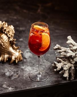 Een vooraanzicht gekleurde cocktail in glas op het donkere oppervlak drinkt sapfruit
