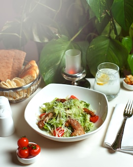 Een vooraanzicht gekookt maaltijd met plakjes vlees en groenten in witte plaat op de witte tafel