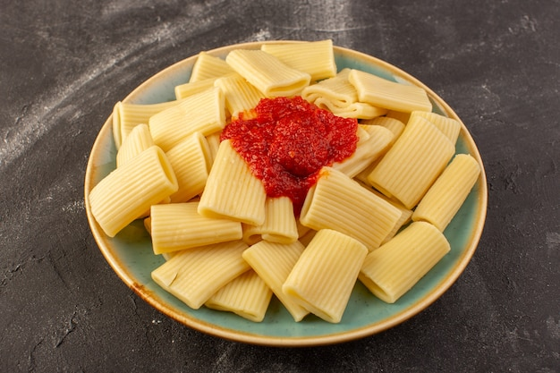 Een vooraanzicht gekookte italiaanse deegwaren met tomatensaus binnen plaat op de grijze italiaanse het voedselmaaltijd van lijstdeegwaren