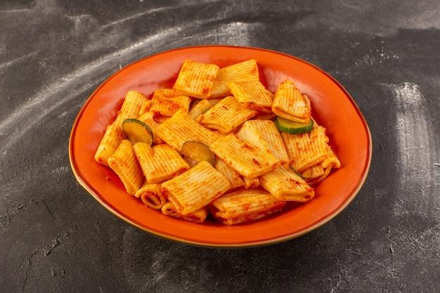 Een vooraanzicht gekookte italiaanse pasta met tomatensaus en komkommer in plaat op het donkere oppervlak
