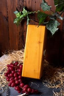 Een vooraanzicht gele doos sloot samen met rode druiven en groene bladeren op de bruine achtergrondwijnmakerijvruchten bessen