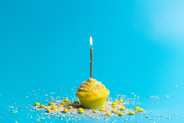 Een vooraanzicht gele verjaardagstaart met kaars op blauw