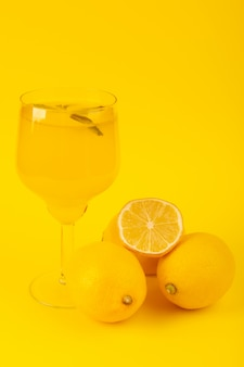 Een vooraanzicht gele verse citroenen vers rijp geheel en gesneden met citroendrank binnen glasvruchten die op de gele achtergrondcitrusvruchtenkleur worden geïsoleerd
