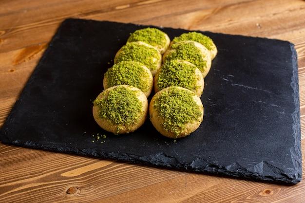 Een vooraanzicht gepoederde koekjes om deeg zoete yummy op de zwarte met weefsel beklede zoete koekjesbakkerij