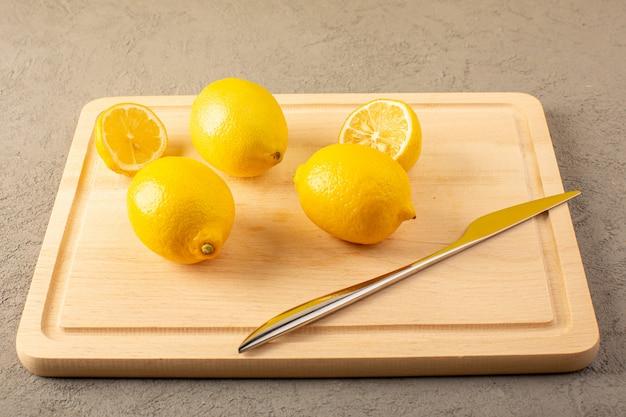 Een vooraanzicht gesloten gele verse citroenen rijp mellow sappig opgedoken op het crème bureau bekleed en gesneden op het grijs