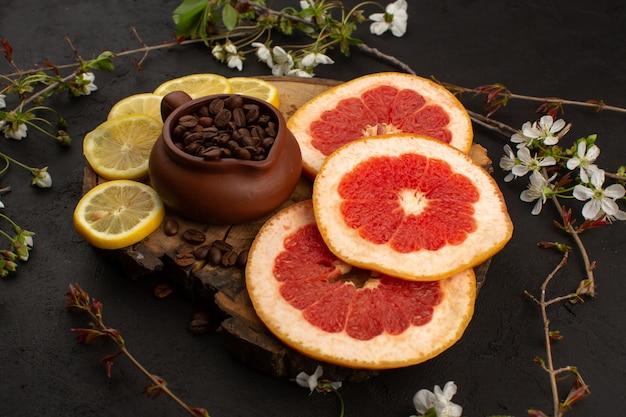 Een vooraanzicht gesneden citrusvruchten zoals citroenen en grapefruits samen met koffiezaden op de donkere vloer