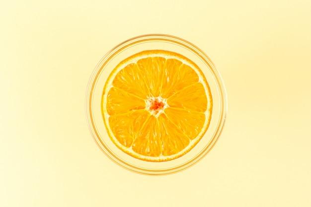 Een vooraanzicht gesneden oranje ronde verse sappige mellow en verse binnenkant ronde transparante kom geïsoleerd op de crème gekleurde achtergrond exotische citrusvruchten