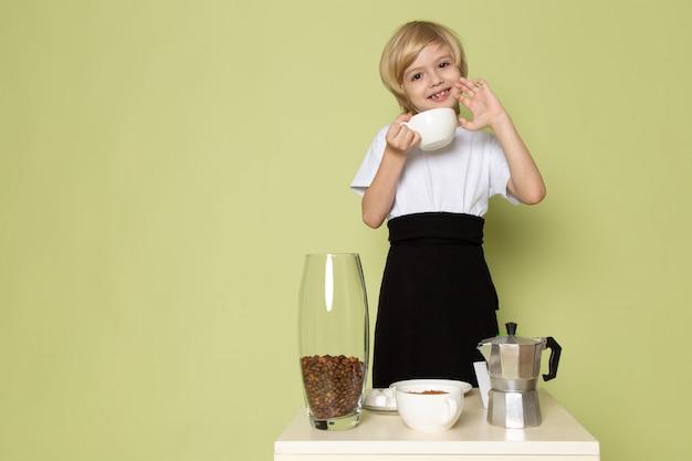 Een vooraanzicht glimlachende blonde jongen die in witte t-shirt koffie voorbereidt dichtbij de lijst aangaande het sotne gekleurde bureau