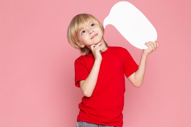 Een vooraanzicht glimlachende blondejongen die wit teken in rode t-shirt op de roze ruimte houdt
