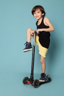 Een vooraanzicht glimlachende jongen in zwarte t-shirt berijdende autoped op de blauwe vloer