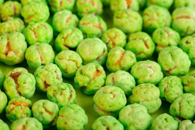 Een vooraanzicht groene snoepjes geïsoleerd getextureerde zoete lekker op de groene achtergrond zoetheid banketbakkerij bon-bons