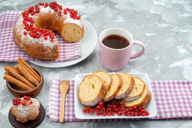 Een vooraanzicht heerlijke cake met verse rode amerikaanse veenbessen kaneel en thee op de witte van de het koekje van de bureaucake de bessensuiker
