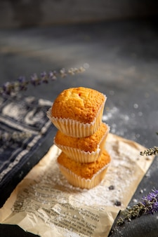 Een vooraanzicht heerlijke kleine cakes met paarse bloemen op de grijze tafel koekjes thee koekje zoete suiker