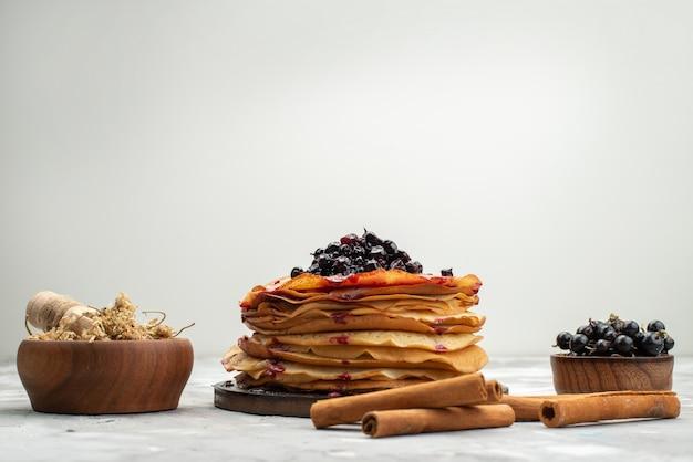 Een vooraanzicht heerlijke ronde pannenkoeken lekker en rond gevormd met bosbessen en kaneelpannekoek gebak koken
