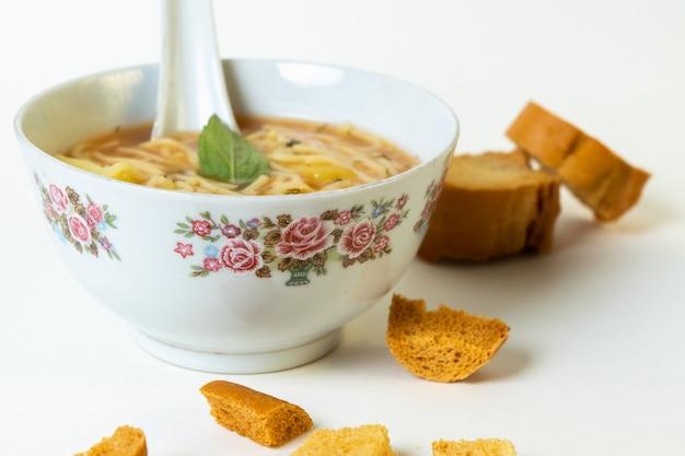 Een vooraanzicht hete soep met groenten in witte platen, samen met sneetjes brood op wit