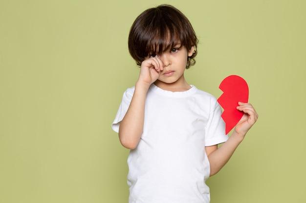 Een vooraanzicht huilende schattige jongen in wit t-shirt op de steen gekleurde ruimte