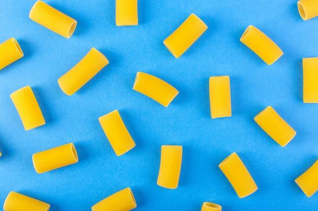 Een vooraanzicht isoleerde gele weinig ruw deegwaren op de blauwe de spaghettideegwaren van de achtergrondvoedselmaaltijd