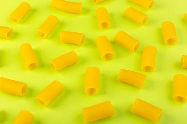Een vooraanzicht isoleerde gele weinig ruw deegwaren op de groene de spaghettideegwaren van de achtergrondvoedselmaaltijd