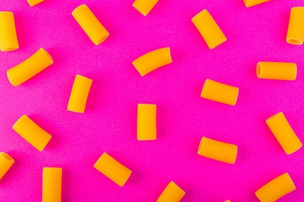 Een vooraanzicht isoleerde gele weinig ruw deegwaren op de purpere de spaghettideegwaren van de achtergrondvoedselmaaltijd
