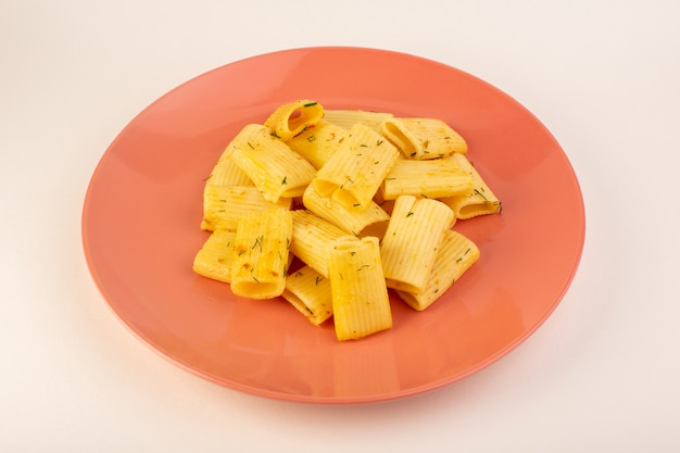 Een vooraanzicht italiaanse pasta met gedroogde groene kruiden in roze plaat op wit