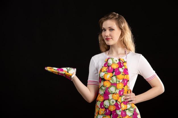 Een vooraanzicht jong aantrekkelijk meisje die in kleurrijke kaap dragend schoonmakende handschoenen op de zwarte schoonmakende huisvrouw dragen als achtergrond