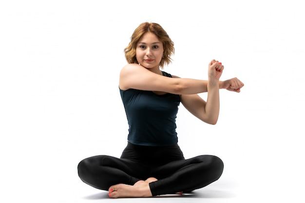 Een vooraanzicht jong aantrekkelijk meisje in blauw overhemd en de zwarte uitrusting die van de broekensport trainingen doen die op het wit glimlachen