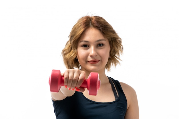 Een vooraanzicht jong aantrekkelijk meisje in blauw overhemd en zwarte broeken sportuitrusting die trainingen met domoren op het wit doen