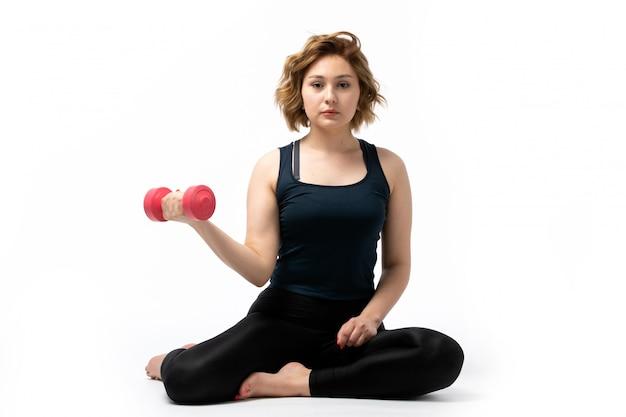 Een vooraanzicht jong aantrekkelijk meisje in blauw overhemd en zwarte broeken sportuitrusting die trainingen met dumbells op het wit doen