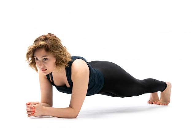 Een vooraanzicht jong aantrekkelijk meisje in blauw overhemd en zwarte broeken sportuitrusting die trainingen op het wit doen
