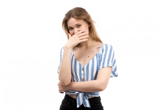 Een vooraanzicht jong aantrekkelijk meisje in gestreept blauw-wit t-shirt dragen zwarte jeans poseren proberen niet te lachen op het wit